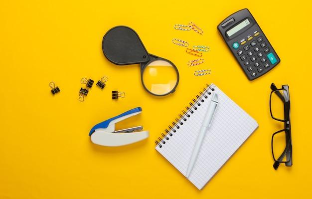 Outils de bureau, papeterie. agrafeuse, calculatrice, loupe, trombones, cahier sur fond jaune.