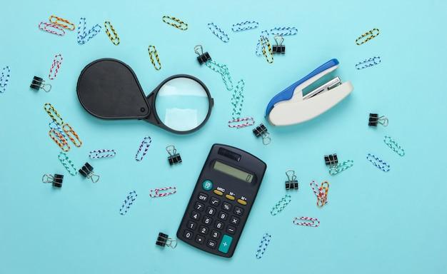 Outils de bureau, papeterie. agrafeuse, calculatrice, loupe, trombones sur un pastel bleu.