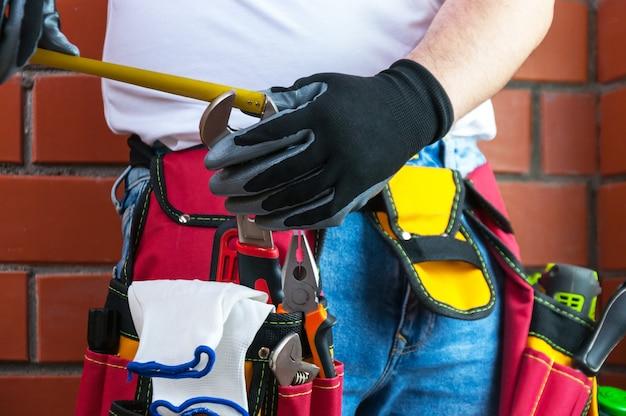 Des outils à la ceinture pour les outils. le constructeur mesure le diamètre de la clé avec un ruban à mesurer.