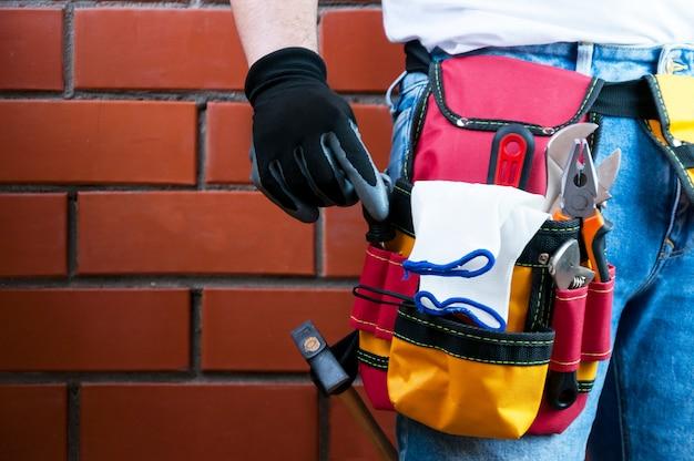 Des outils à la ceinture pour les outils. le constructeur tient un tournevis.