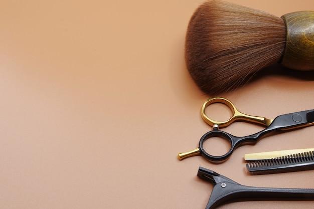 Outils de coiffeurs isolés sur fond marron avec espace de copie pour votre texte ciseaux de coiffeurs et épingles à cheveux