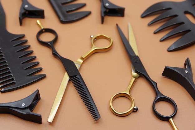 Outils de coiffeurs professionnels isolés sur fond marron peigne à ciseaux de coiffeurs et épingles à cheveux