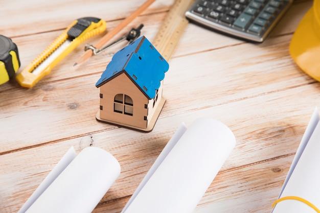Outils de conception et une petite maison sur une table en bois