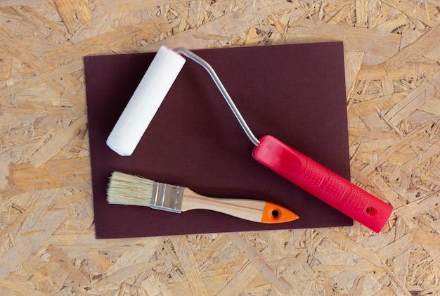 Outils de construction - brosses, rouleaux, spatules et papier de verre sur fond de béton