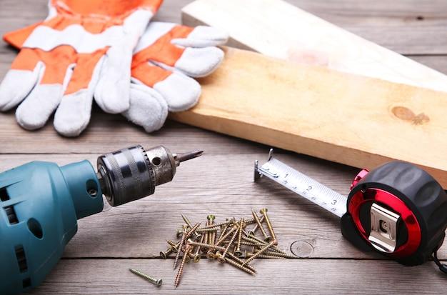 Outils de construction sur un bureau en bois gris.