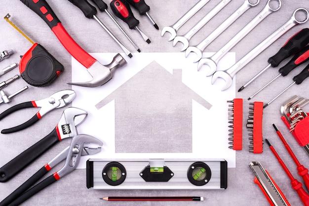 Outils de construction et de réparation autour d'une maison blanche en papier sur un mur gris prêt financier, concept d'entretien de réparation