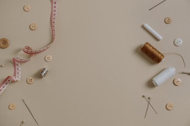 Outils de couture : boutons, bobine, dé à coudre, mètre ruban, aiguilles sur beige neutre