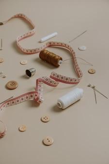 Outils de couture : boutons, bobine, dé à coudre, mètre ruban sur beige neutre