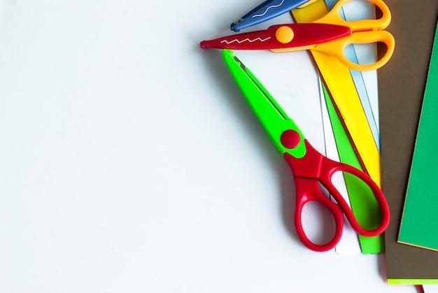 Outils créatifs pour enfants. ciseaux bouclés et feuilles de couleur fond