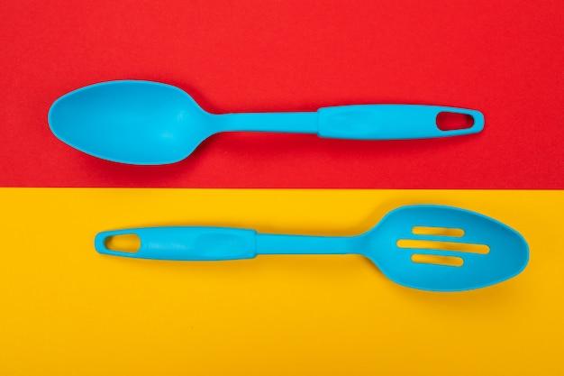 Outils de cuisine en plastique isolé sur jaune rouge