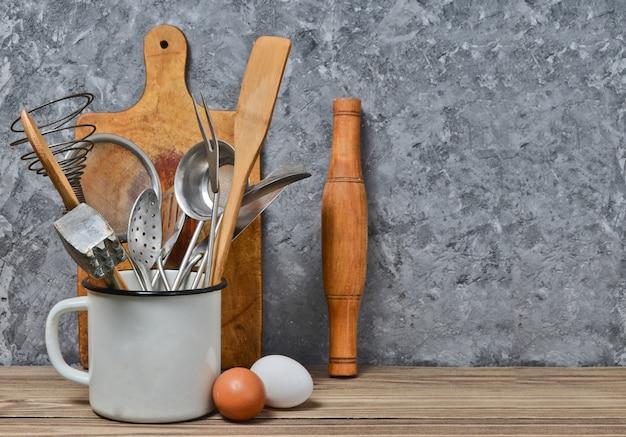 Outils de cuisine pour cuisiner sur une table en bois sur le fond d'un mur en béton. cuillère, fourchettes, spatule en bois, rouleau à pâtisserie, œufs.