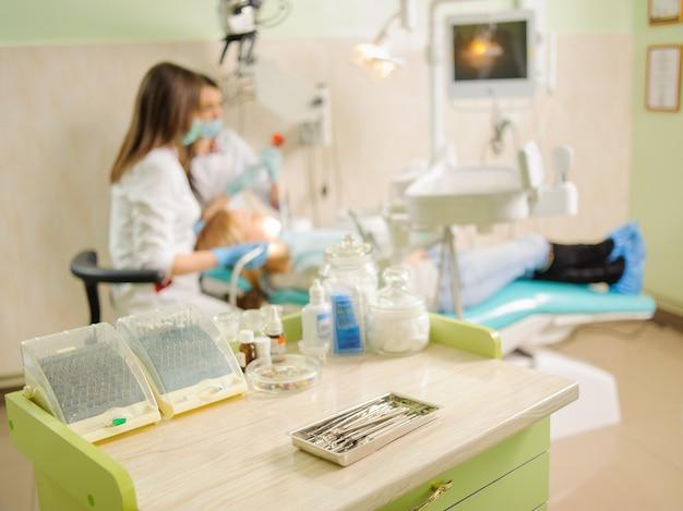 Les outils dentaires à l'avant-plan et le dentiste effectuant le premier bilan