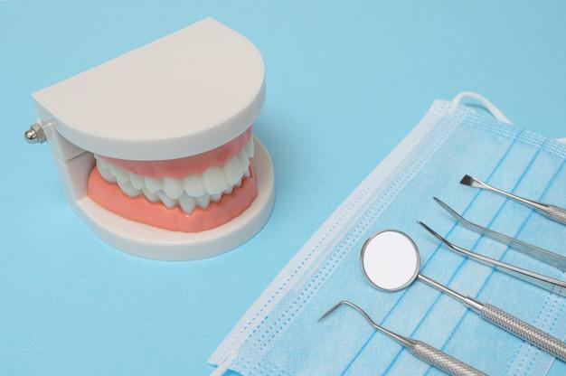 Outils dentaires sur fond bleu. concept de technologie médicale. hygiène dentaire. concept de guérison. outils de dentiste. matériel dentaire.