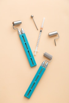 Outils de dermatologie dermaroller de cosmétologie, mesoscooter pour la cosmétologie matérielle, seringue pour les injections de santé des jeunes dans le corps du visage. les outils de traitement des soins de la peau des cosmétologues sont à plat sur fond beige.