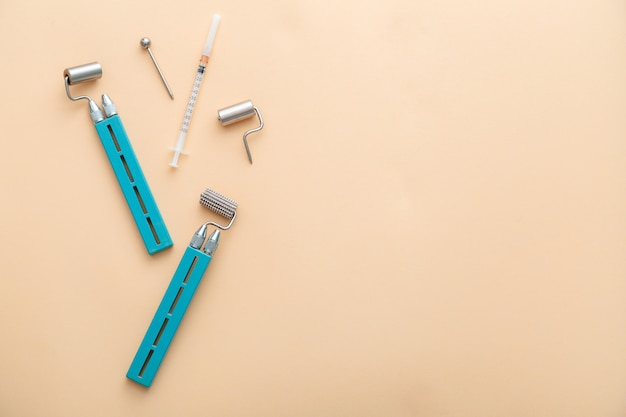 Outils de dermatologie dermaroller de cosmétologie mesoscooter pour seringue de cosmétologie pour injections de jeunes dans les outils de traitement de soins de la peau cosmétologues du corps à plat sur fond beige espace de copie