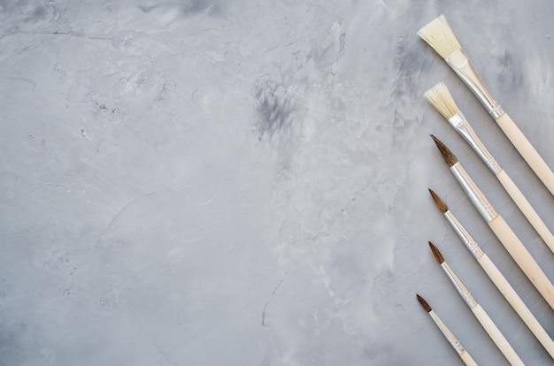 Outils de dessin, ensemble de pinceaux propres sur fond gris.