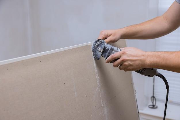 Outils électriques à main d'angle sur la coupe de plaques de plâtre