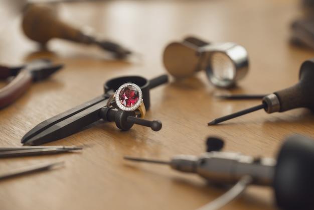 Outils et équipement pour le travail des bijoux sur un bureau en bois antique.