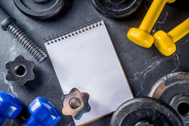 Outils de fitness et haltères avec cahier vierge