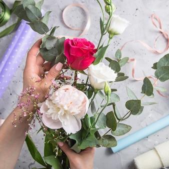 Outils de fleuriste et lieu de travail avec des rubans, des fleurs et des ciseaux