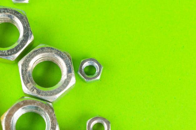 Outils d'ingénierie. boulons et écrous sur fond vert