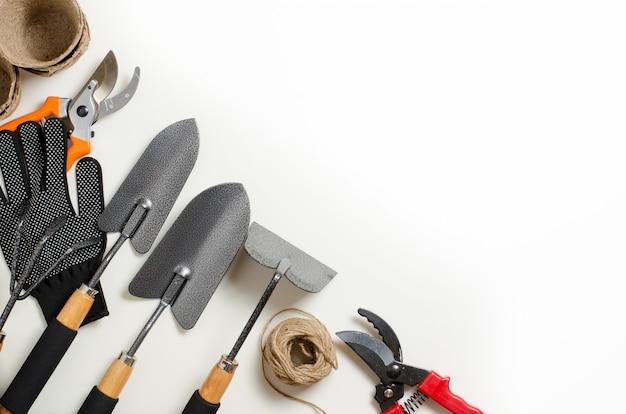 Outils de jardin et des gants sur un fond blanc. espace pour le texte
