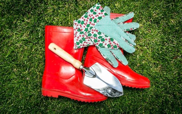 Outils de jardin en gros plan et bottes en caoutchouc rouges allongées sur l'herbe verte fraîche
