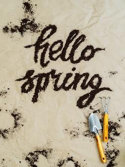 Outils de jardin avec inscription hello spring de la terre sur du papier kraft froissé. concept de printemps.