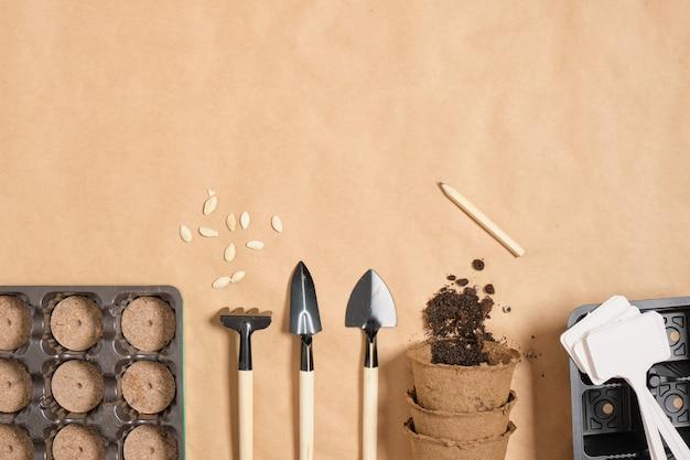 Outils de jardin sur papier kraft copie espace vue de dessus, petites plaques de spatules et pots de tourbe comprimés, tout pour planter des semis