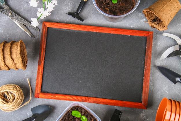 Outils de jardin et des pots sur un fond de béton gris. tableau de craie. vue de dessus, espace de copie.