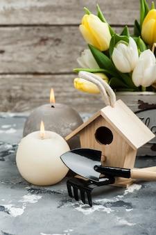 Outils de jardinage, fleurs, bougies allumées
