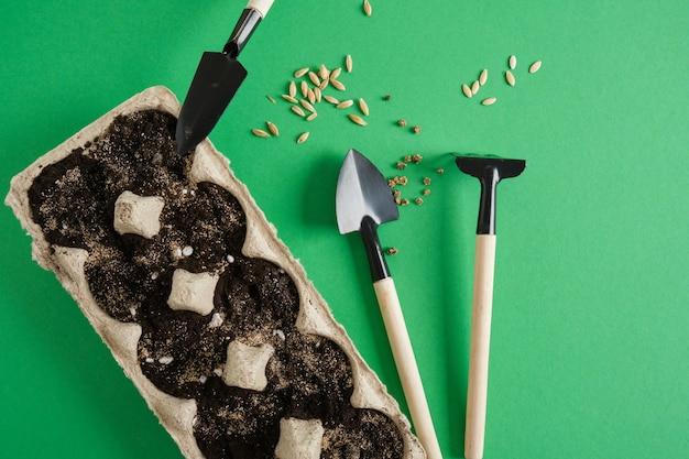 Outils de jardinage sur fond vert. petites pelles et râteaux pour planter des semis et des plantes d'intérieur, concept de jardinage écologique