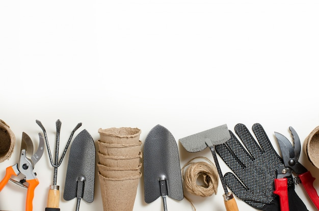 Outils de jardinage et gants sur fond blanc
