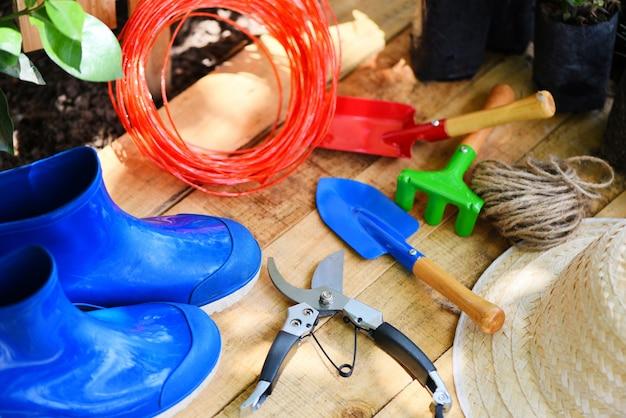 Outils de jardinage sur une planche en bois avec un sécateur, une corde, une botte en caoutchouc, une truelle de jardin