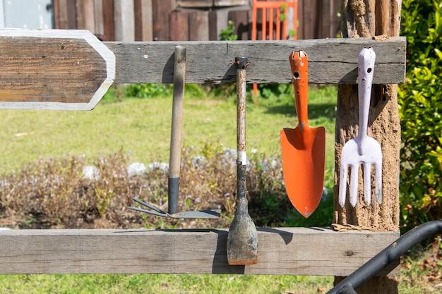 Outils de jardinage suspendus à un rail en bois