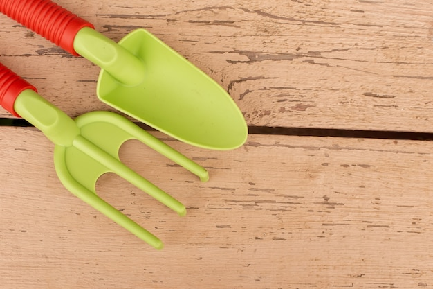 Des outils à main de jardin vert clair, une pelle et un râteau avec des poignées orange, reposent sur des planches peintes.