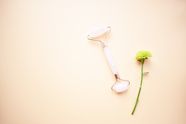 Outils de massage facial rose gua sha. rouleau de jade en quartz rose. traitement anti-âge, liftant et tonifiant à domicile. copiez l'espace. vue de dessus. mise à plat.