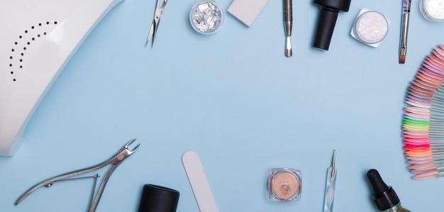 Outils et matériaux pour manucure à plat avec espace de copie sur une surface bleue
