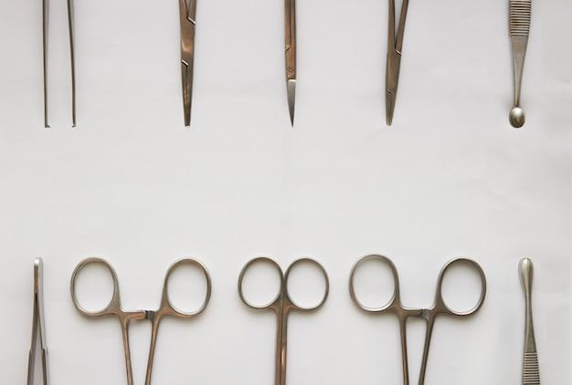 Outils de médecin, curetage, crampes, forceps et ciseaux sur blanc isolé