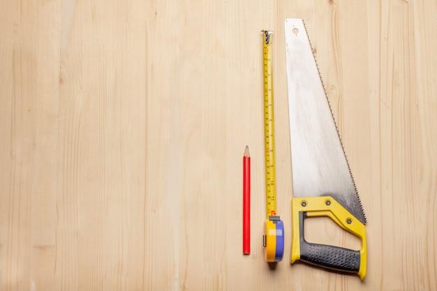 Outils de menuisier - règle, scie, crayon sur table en bois