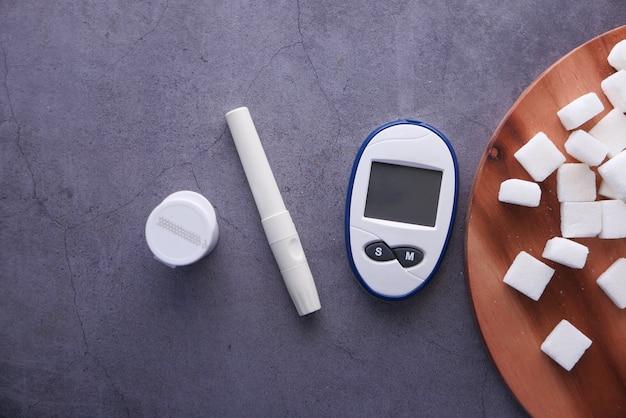 Outils de mesure diabétique et cube de sucre ob fond noir