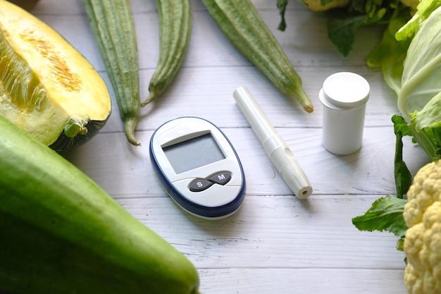 Outils de mesure diabétique et légumes frais sur table.