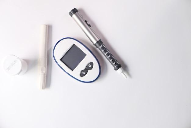 Outils de mesure diabétique et stylo à insuline sur table.