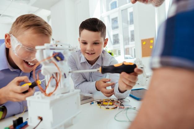 Des outils modernes. joyeux jeune garçon souriant tout en utilisant un tournevis