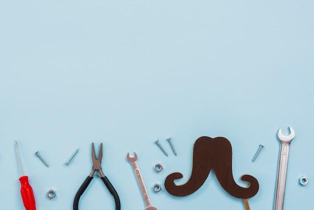 Outils avec moustache de papier noir sur la table