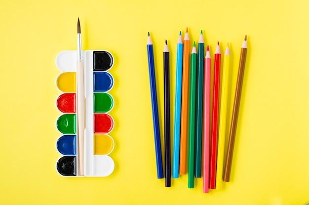 Outils de peinture. aquarelle, pinceau et crayons de couleur sur fond jaune