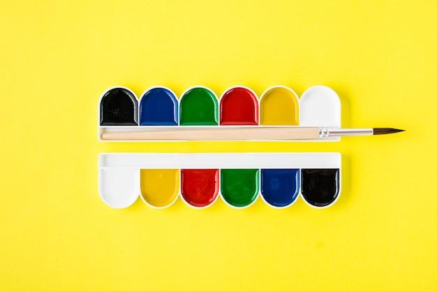 Outils de peinture. aquarelle et pinceau sur un jaune