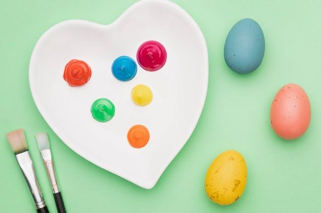Outils de peinture et oeufs colorés