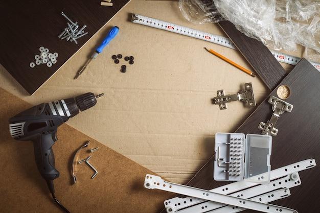 Outils, pièces d'ameublement, film d'emballage, vis sur une feuille de carton. construction manuelle de meubles. atelier de concept. mise à plat, vue de dessus
