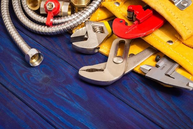 Outils de plomberie dans le sac jaune et pièces de rechange